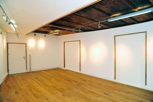 In einem Raum im zweiten Obergeschoss wird ein Teil der freigelegten Deckenvertäfelung zu einem Schaufenster in die Geschichte des Hauses
