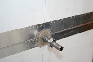Zwischen die Platten werden Stabanker gesetzt, um Schienen für die vorgehängte Fassade zu befestigen