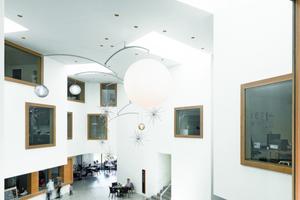"""Die Eingangshalle ist das Herz des Altersheims. Durch fünf trichterförmige Oberlichter fällt Tageslicht in den rund 12 m hohen Raum, in den die Bewohner durch große """"Guckkästen"""" mit Eichenholzrahmen schauen können<br />Foto: Roger Frei"""