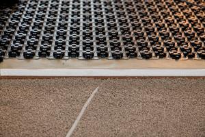 Alle Schichten auf einen Blick: Auf dem Leichtausgleichmörtel liegen eine Trittschall-Holzfaserdämmung und eine Wärmedämmung aus Polystyrol, darüber die Schrenzlage und die Noppenplatten der Heizung