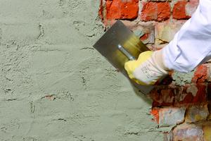 Das Mauerfugennetz wird mit weber.tec 933 verschlossen. Dann bildet der Handwerker eine Hohlkehle und kämmt die Haftbrücke horizontal auf