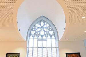 Die mit gelochten GK-Platten beplankte Decke schmiegt sich in der Nürnberger St. Jakobskirche gleich einer Jakobsmuschel um das  gotische Maßwerkfenster Foto: Thilo Jaeckel / Vogl Deckensysteme