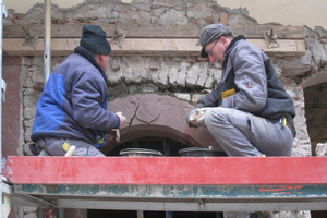 Mauerer setzen den Torbogen in die ursprüngliche Öffnung ein
