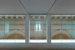 Die Sandsteinfassade des Altbaus wird im Übergang zum Anbau zur Innenwand, seitlich gefasst von einer gläsernen Fuge<br />Foto: Stefan Müller<br />