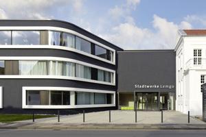 Der dunkle Erweiterungsbau (links im Bild) steht im Kontrast zum weißen Bestand (rechts im Bild). Verbindendes Elemente sind die weißen Metallrahmen der Fensterbänder am Neubau