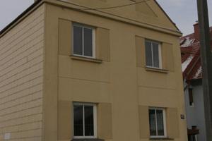 Echtbild eines Hauses. Schwachstellen werden mit Hilfe einer Wärmebildkamera sofort sichtbar: Heizkörpernischen sind nicht richtig gedämmt, Reflexion vom kalten Himmel im rechten oberen Fenster