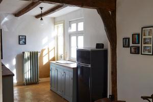 Blick in die heutige Wohnküche in Richtung Innenhof. Gusseiserner Heizkörper an der Hausrückwand. Das homogene Fliesenbild ist deutlich sichtbar