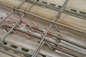 Mit Sprühlack werden auf der Folie erst die Positionen der Schubverbinder markiert, dann werden diese im 45°-Winkel eingeschraubt