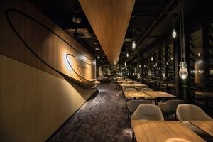 """Die geschwungen geformte Wandverkleidung im Restaurant """"Symphonie"""" besteht aus 16 mm dickem Eurodekor MDF im Dekor Esche Cassino braun gefertigt"""