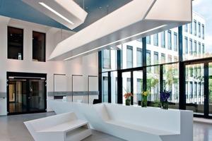 Links: Die gebaute Markenidentität ist auch in der neuen Xella Hauptverwaltung unter anderem im Foyer am X-förmigen Empfangstresen und der darüber schwebenden X-förmigen Leuchte zu erkennen<br />