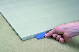 """Nach dem Auftrag des Nutklebers wird der Flachdübel durch den """"Klebervorhang"""" in die Nut geschoben. Durch den Einsatz des Flachdübels erfolgt automatisch eine Höhenfixierung, so dass die Bodenplatten eine ebene Oberfläche bilden"""