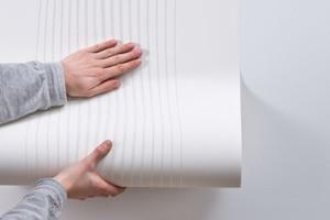 Kleister gleichmäßig auf die Wand auftragen und die Relieftapete auf Stoß ins nasse Kleisterbett einlegen