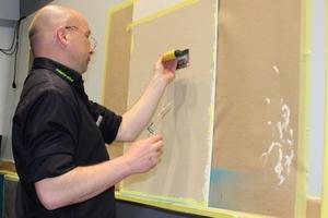 Ein Mitarbeiter der Firma Caparol zeigt auf der Mega-Messe in Hamburg kreative Putztechniken