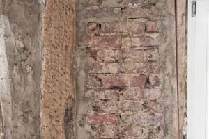 Vor der Verarbeitung des Lehmmörtels entfernen die Handwerker die alten Holzwolle-Leichtbauplatten