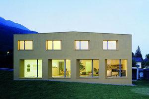 Mit großen Fenstern in der goldenen Fassade öffnet sich das Einfamilienhaus in Azmoos für einen Ausblick in die grandiose Landschaft