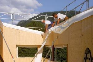 Die Zimmerleute bei der Vorbereitung zur Montage der massiven Dachelemente<br />